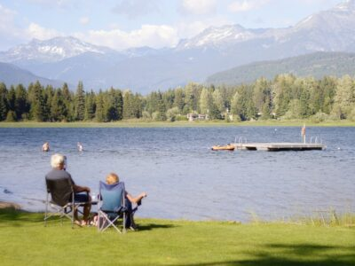 older couple sitting in lawn chairs staring at a lake